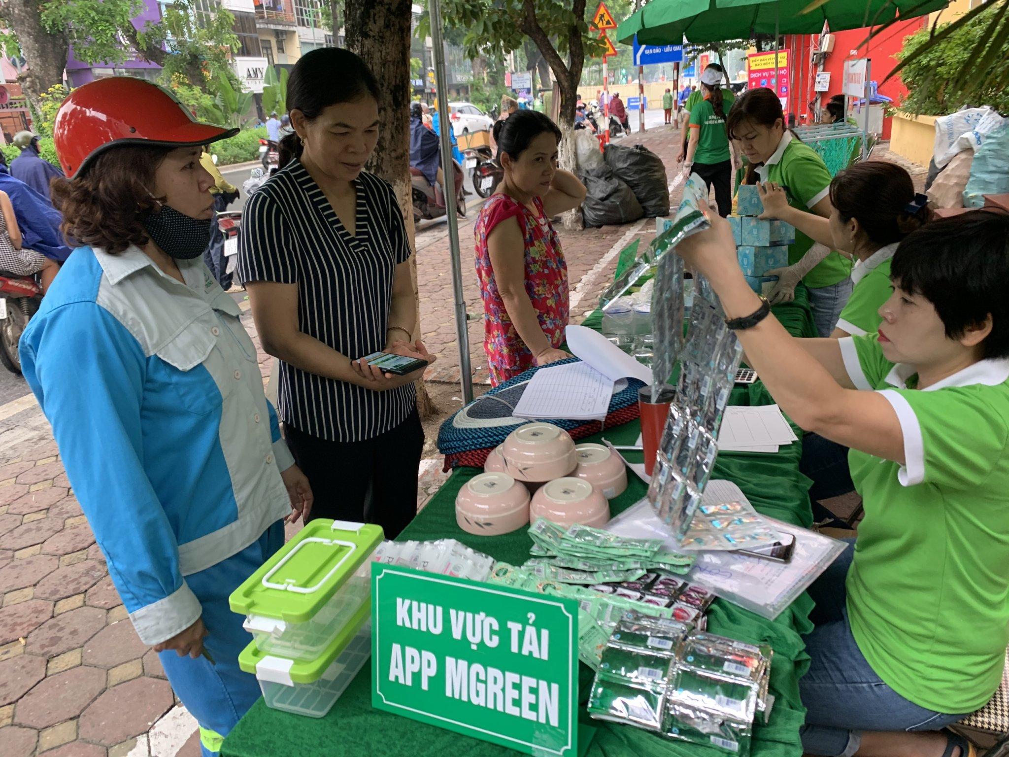 Người dân sử dụng App mGreen để tích điểm khối lượng rác tái chế và nhận quà tại các Điểm (GreenHub) cân rác đổi quà của mGreen tại Phường Lý Thái Tổ, quận Hoàng Kiếm